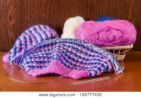 Natural woolen yarn and knitting on wooden background. Selective focus