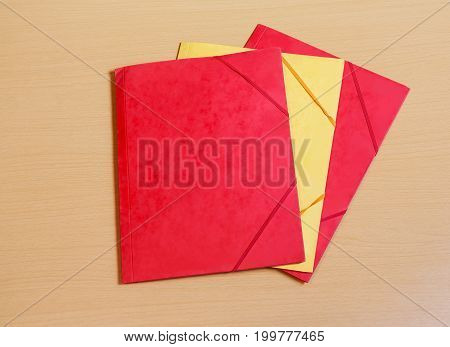 Red and yellow office folders on desk