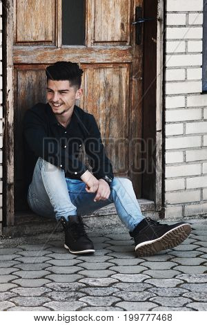 smiling young man sitting on threshold and watching sideways