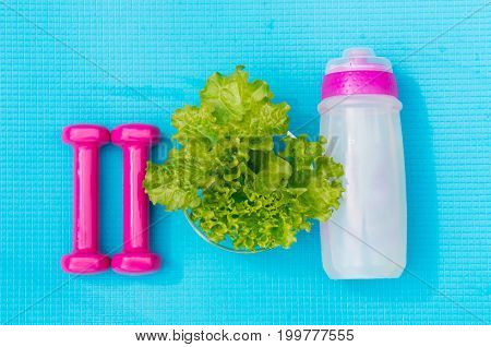 Fitness healthy and active lifestyles concept. Dumbbells bottle of water and salad leaves on yoga mat