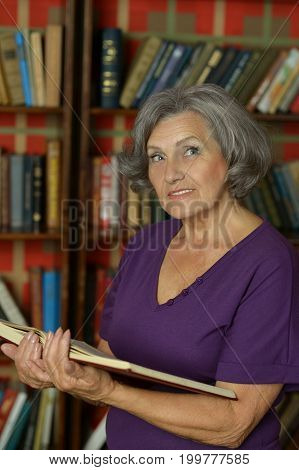 Portrait of a beautiful senior woman reading in library