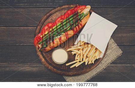 Hot dog and french fries. American fast food restaurant cuisine on wooden platter on table, top view