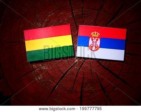 Bolivian Flag With Serbian Flag On A Tree Stump Isolated