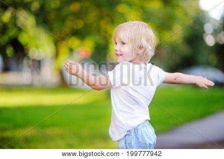Cute Little Boy Having Fun In Sunny Summer Park