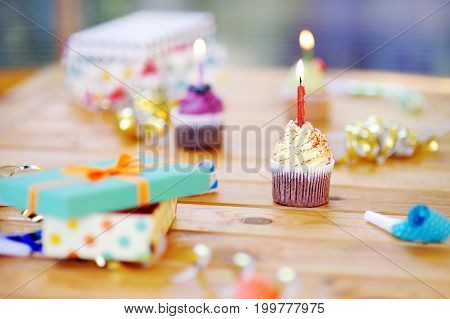 Birthday party with colorful decoration and cakes with candles. Closeup photo with sweets confetti candy whistle/blower/horn and festive gifts.