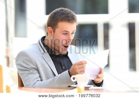 Portrait of an amazed executive reading a letter sitting in a coffee shop