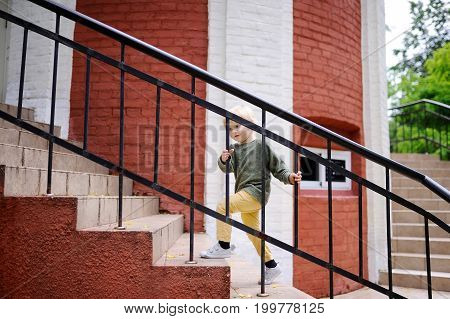 Little Boy Walking Up On The Stairs Outdoors