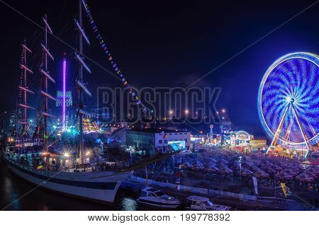 SZCZECIN, WEST POMERANIAN / POLAND - 2017: Final Tall Ships Races. Sailing vessel MIR and ferris wheel on the harbor quay at night