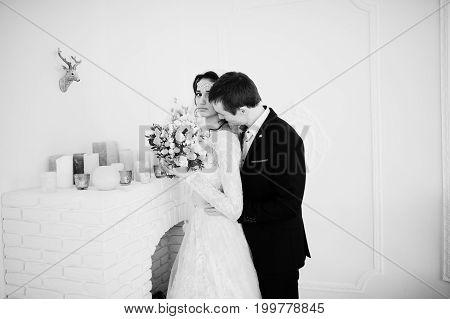 Wedding Couple Posing In The Light White Studio. Black And White Photo.