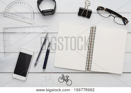 Modern office background. Stationery, open notepad, smart watch, glasses and mobile on white wooden table. Top view on stylish workspace with copy space on blank textbook