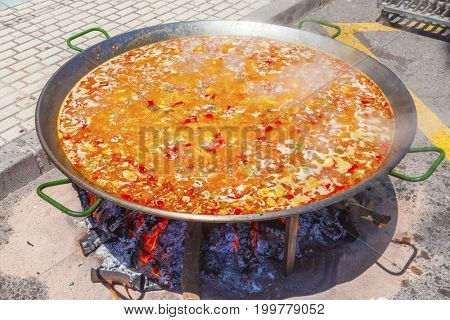 Paella from chicken, vegetables and rice. The national Spanish dish of paella in a large skillet is cooked on an open fire, at the stake