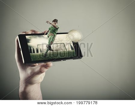Hand holding a smartphone which displays a soccer match on the touch screen. Soccer player shooting the ball and getting out of the screen.