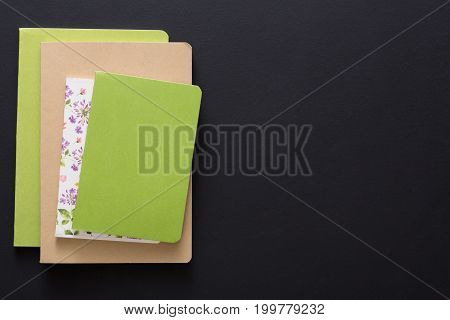 Stylish mockup with set of colorful notebooks on black background with copy space, flat lay, concept of start-up and stationery supplies