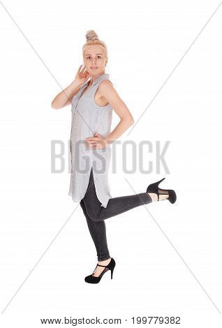 A lovely young woman standing in tights and a dress in profile with blond hair isolated for white background