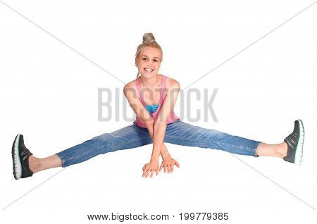 A beautiful young woman sitting on the floor with her legs spread out in jeans isolated for white background