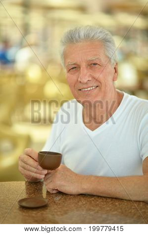 Portrait of a mature man with cup in cafe