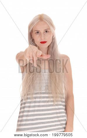 A beautiful young blond woman in a dress pointing her finger at the photographer looking serious isolated for white background