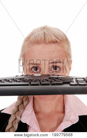 A beautiful business woman with blond braided hair and big eyes holding the keyboard over her face isolated for white background