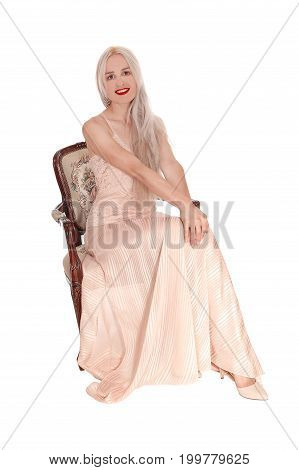 A beautiful blond woman in a pink evening dress sitting in an old armchair smiling isolated for white background