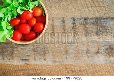 Fresh tomato and lettuce in wood bowl put on wood table. Top view or flat lay of tomato and green oak lettuce with copy space for background. Fresh green oak lettuce and tomato prepare for cooking.
