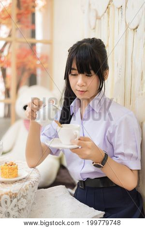 Cute Asian Thai high school girl in uniform is preparing her tea in a lovely cafe in room in schoolgirl fashion and food and drink concept.