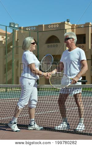 senior couple shaking hands over net after tennis game