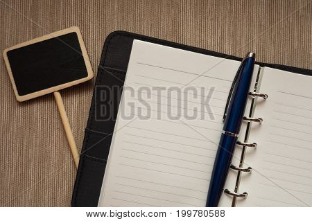 Opened memo book with blue pen and small post are set in top view.