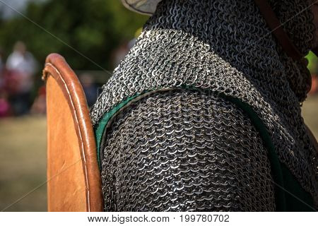 Medieval knight reenactment with costumed characters and medieval armor detail chainmail, helmet and shields. Medieval demonstration and recreation