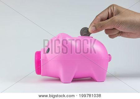 Inserting Thai coin to the pink piggy bank.
