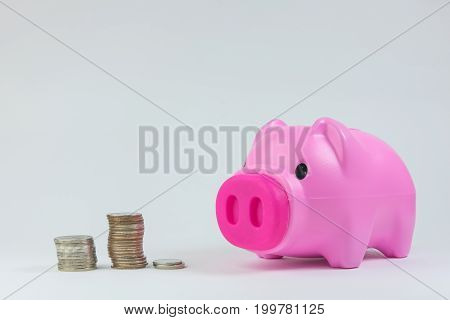 Pink piggy bank with coins in white background.