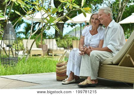 Happy senior couple sitting on chaise lounge at resort