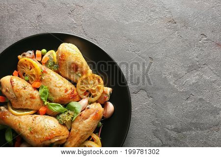 Plate with delicious roasted chicken drumsticks and lemon on grey table