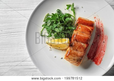 Plate with delicious fish in bacon and arugula on table