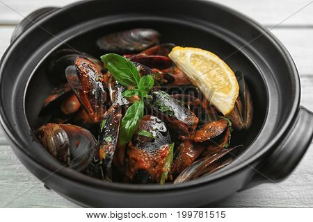 Pan with delicious mussels in tomato sauce, closeup