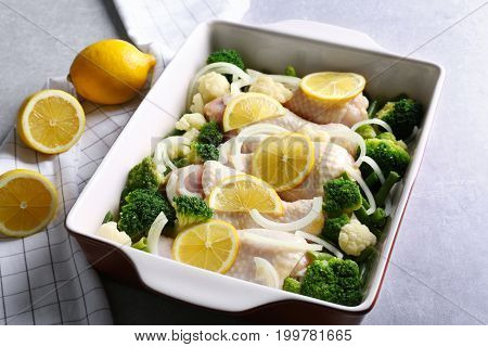 Raw chicken drumsticks with lemon and broccoli in baking dish on grey table