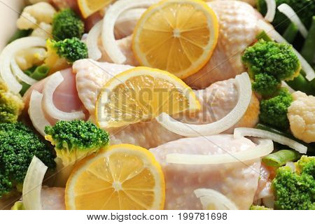 Raw chicken drumsticks with lemon and broccoli, closeup