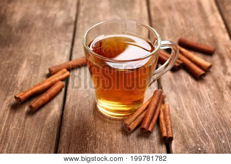 Cup with aromatic hot cinnamon tea on wooden table