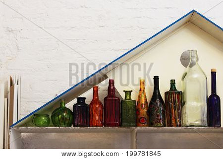 Creative space. A cozy home interior of a multitude of different bottles of different shapes in an open cupboard against a white brick wall.