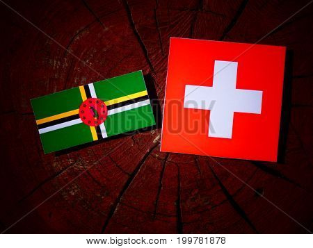 Dominica Flag With Swiss Flag On A Tree Stump Isolated