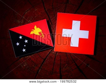 Papua New Guinea Flag With Swiss Flag On A Tree Stump Isolated