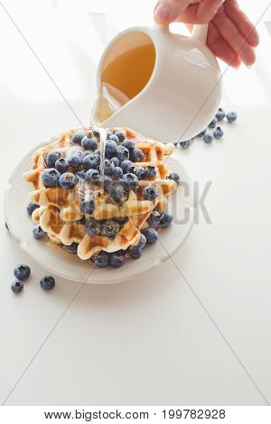Cropped Shot Of Woman Pouring Syrup From Saucer On Tasty Waffles