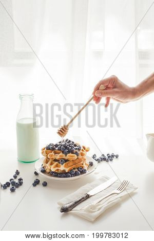 Cropped Shot Of Woman Pouring Honey On Delicious Waffles