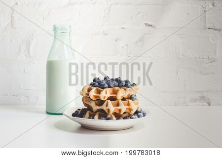 Delicious Breakfast Of Stacked Fresh Waffles With Blueberries And Milk
