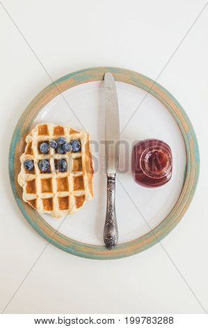Top View Of Waffle With Jam, Blueberries And Knife On Vintage Plate