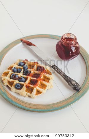 Tasty Waffle With Jam, Blueberries And Knife On Vintage Plate