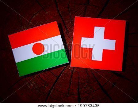 Niger Flag With Swiss Flag On A Tree Stump Isolated