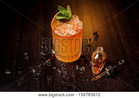 small skull-shaped bottle and summer cocktail with mint leaves and orange slice