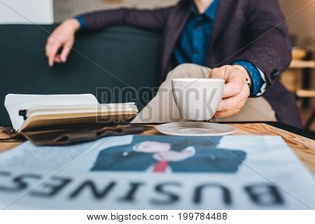 partial view of businessman in suit resting on sofa in cafe