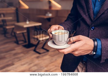 partial view of businessman holding cup of coffee in hands in cafe