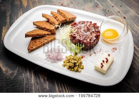Beef tartare with arugula salad egg yolk and crisp bread chips on white plate close up